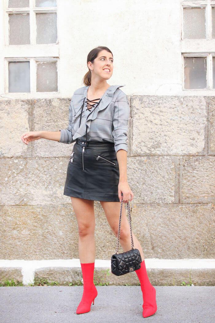 Blusa de cuadros, estampado príncipe de gales. Falda negra de piel. Botines rojos estilo calcetín de Zara.