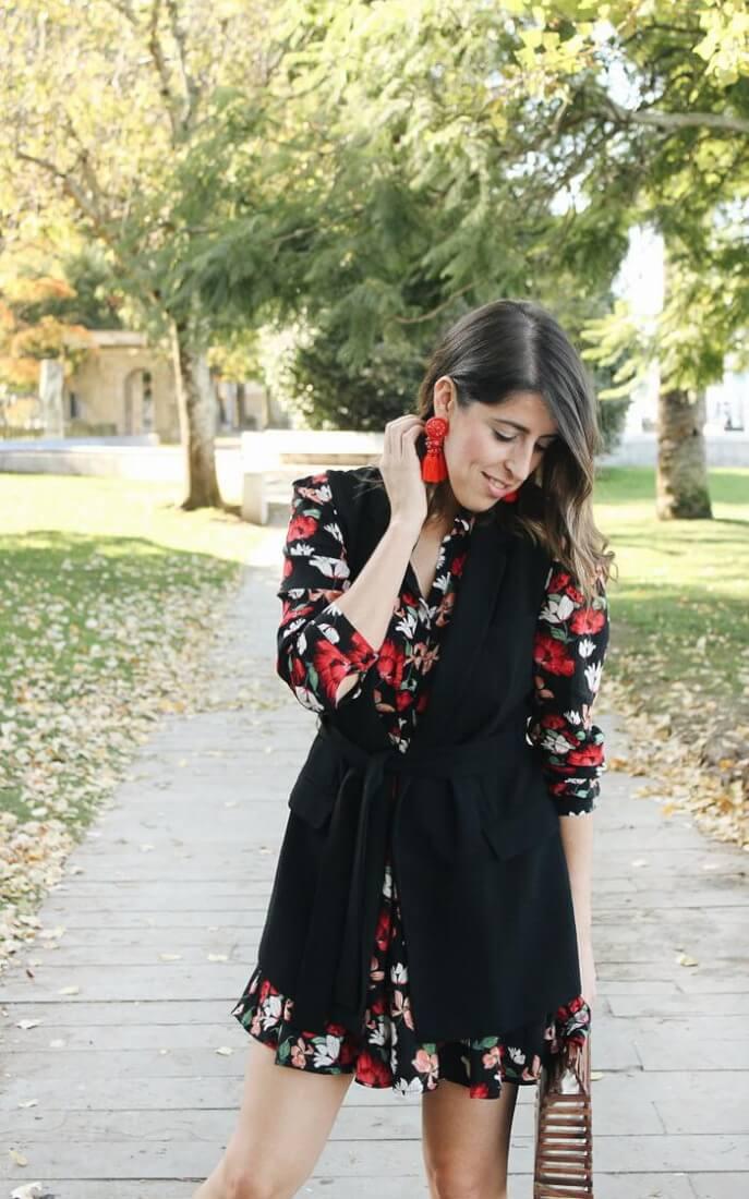 Vestido estampado floral de Zara con chaleco negro y pendientes rojos