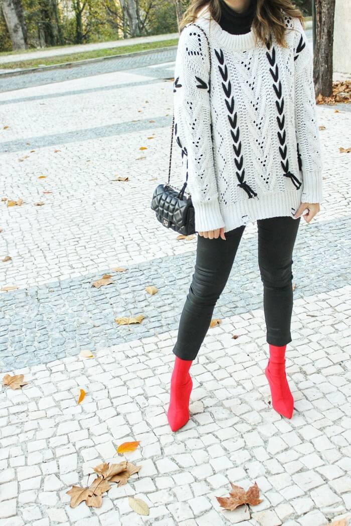 Look con jersey con cordones, pantalón negro y botines calcetín.